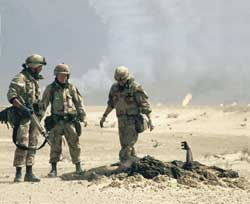 American soldiers looking at  the carbonized body of an Iraqi soldier during Operation Desert Storm in 1991.