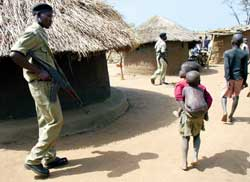 a Ugandan police patrol in the village of Pabo, near Gulu; above, the training of a child-soldier