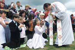 A girl receives the Eucharist during the mass presided by the Pope at Chayka airport