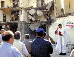 A Chaldean priest prays among  the ruins of the headquarters of the UN in Baghdad, destroyed by the attack of 19 August in which senior official Sergio Vieira de Mello and another 22 people were killed