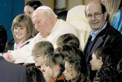 Left, John Paul II with Ernesto Olivero during an audience in the Paul VI Hall on 31 January 2004, on the fortieth anniversary of SERMIG; right, Palestinian children watch a demonstration of Orthodox Jews in the old city of Jerusalem.