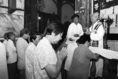 Faithful kneeling during Communion in the church of Nantang in Beijing