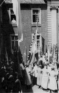 Von Galen alla finestra del Palazzo vescovile saluta un gruppo di giovani con le bandiere delle loro associazioni