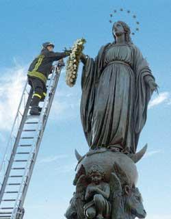 Un pompier dépose la couronne de fleurs sur la statue de l'Immaculée Conception de la place d'Espagne, à Rome, à l'occasion de la fête du 8 décembre