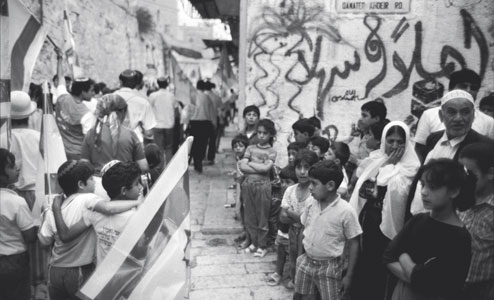 Palestinian children watch a demonstration of Orthodox Jews pass by in the Old City of Jerusalem [© Magnum/Contrasto]