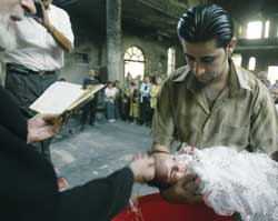 A baptism in a Catholic church of Baghdad that still bears the marks of the fire in October which all but destroyed it