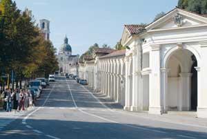 Os pórticos que ligam a cidade de Vicenza ao santuário: a obra, finalizada em 7 de março de 1746 pelo arquiteto Francesco Muttoni, se desdobra por 700 metros e 150 arcadas, como o número de contas do Rosário. Estas foram repartidas em grupos de 10, simbolizando os 15 mistérios. Ao fundo, a fachada oriental do santuário