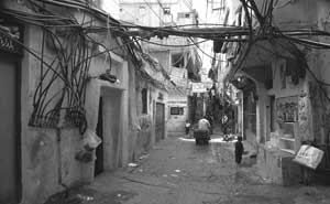 Above, a shot of the Sabra and Chatila Camp in Lebanon. The water pipes and the electric cables interweave dangerously. The light filters with difficulty through the narrow  and constantly wet streets