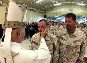 Monsignor Bagnasco, military bishop, administering Confirmation to a soldier in Nassiriya during Christmas mass in 2005