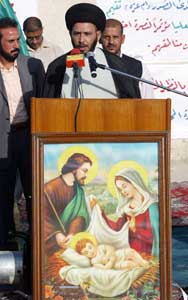 A religious Shiite, affiliated to the group of Moqtada al-Sadr, speaks in front of the church of Saint Elias in Baghdad, 10 June 2007. The Moqtada al-Sadr group distributed humanitarian aid to more than 70 Christian families 