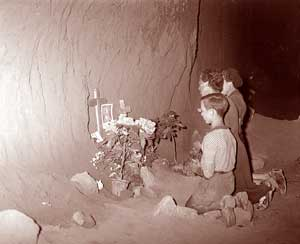 Family members in prayer at an improvised tomb near the Fosse Ardeatine