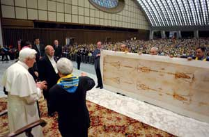 Pope Benedict XVI receiving a present of a copy of the Shroud from the diocese of Turin, in the Paul VI  Hall 2 June 2008. The copy is actual size – 437 cm long by 111 high