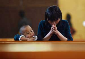 A woman with her son praying in a Catholic church <BR>[© Reuters/Contrasto]