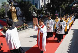 A procession in front of the statue of Matteo Ricci in Beijing [© Associated Press/LaPresse]