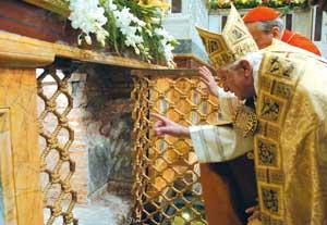 Papa Bento XVI observa o lugar do túmulo de São Paulo, embaixo  do altar central da Basílica de São Paulo Fora dos Muros, através da janela recentemente aberta na cripta