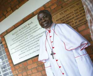 Cardinal Emmanuel Wamala in front of the plaque recording the historic visit 