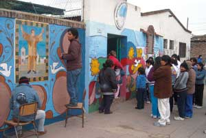 The <I>muraleros</I> of the parish of Nuestra Señora de Caacupé at Villa 21 repaint the mural that portrays Father Daniel de la Sierra, the first pastor of the <I>villa</I>