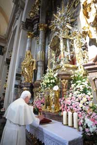 Benedetto XVI in preghiera davanti al Bambino Gesù di Praga, venerato nella chiesa di Santa Maria della Vittoria, il 26 settembre 2009 <BR>[© Osservatore Romano]
