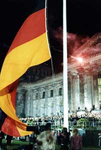 The raising of the German flag in front of the Reichstag building in Berlin during the ceremony to celebrate the re-unification of Germany on the night of 3 October 1990 [© Associated Press/LaPresse]