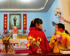 Two girls during a Christmas performance before midnight mass in a Beijing church [© AFP/Getty Images]