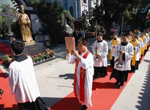 A procession passing the statue of Matteo Ricci in Beijing [© Associated Press/LaPresse]