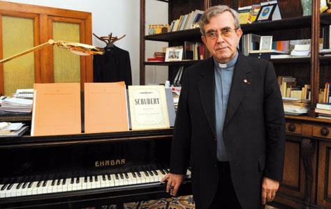 Monsignor Valentino Miserachs Grau, preside del Pontificio Istituto di Musica Sacra, davanti al pianoforte nel suo studio [© Paolo Galosi]