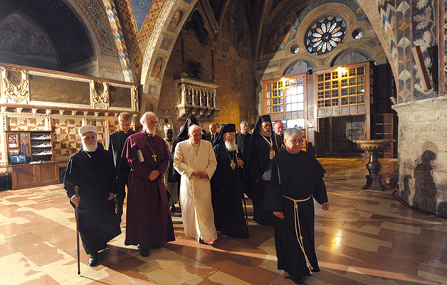 Directed towards the crypt, to venerate the tomb of Saint Francis, Benedict XVI crosses the lower Basilica of Saint Francis with some leaders and representatives of Churches, of Ecclesial Communities and of world religions, at the Assisi meeting, 27 October 2011 [© Osservatore Romano]