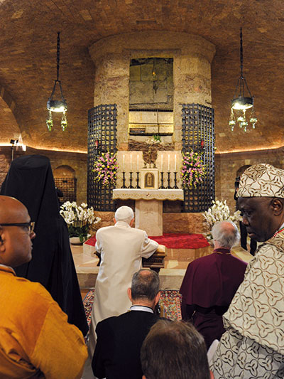 Benedict XVI in prayer at the tomb of Francis in the crypt of the lower Basilica with some leaders and representatives of the Churches, of Ecclesial Communities and world religions [© Osservatore Romano]
