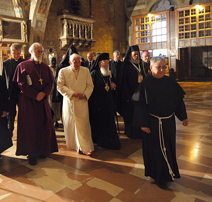 Directed towards the crypt, to venerate the tomb of Saint Francis, Benedict XVI crosses the lower Basilica of Saint Francis with some leaders and representatives of Churches, Ecclesial Communities and of world religions, at the Assisi meeting, 27 October 2011 [© Osservatore Romano]