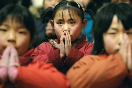 Chinese children in prayer <BR>[© Reuters/Contrasto]